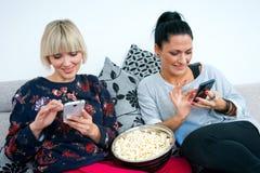 2 привлекательных друз женщины с мобильным телефоном и попкорном Стоковое фото RF