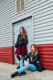 2 привлекательных друз маленькой девочки стоя совместно и представляя на камере Outdoors фасонируйте подругу детенышей портрета д Стоковое Изображение RF