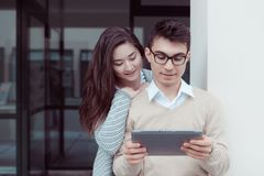2 привлекательных студента уча и смотря в ПК таблетки на кампусе внешнем Стоковые Фотографии RF