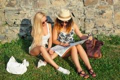 2 привлекательных туриста женщины путешествуя на праздниках в городе Девушки с картой города в поисках привлекательностей Стоковые Изображения RF