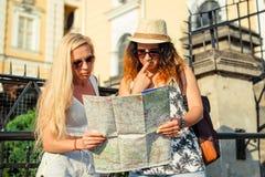 2 привлекательных туриста женщины смотря карту в городе красивейшие детеныши женщины каникулы бассеина принципиальной схемы каник Стоковые Фотографии RF