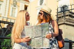 2 привлекательных туриста женщины смотря карту в городе красивейшие детеныши женщины каникулы бассеина принципиальной схемы каник Стоковое фото RF