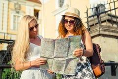 2 привлекательных туриста женщины смотря карту в городе красивейшие детеныши женщины каникулы бассеина принципиальной схемы каник Стоковое Изображение RF