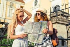 2 привлекательных туриста женщины смотря карту в городе красивейшие детеныши женщины каникулы бассеина принципиальной схемы каник Стоковые Фото