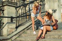 2 привлекательных туриста женщины смотря карту в городе красивейшие детеныши женщины каникулы бассеина принципиальной схемы каник Стоковая Фотография