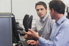 2 привлекательных люд говоря в классе компьютера Стоковое Изображение RF