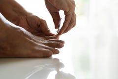 Пригвоздите клиппирование, старшие ногти вырезывания ноги женщины используя клипер ногтя на белой предпосылке, крупном плане стоковое фото rf