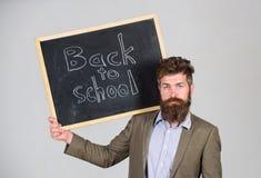 Пригласите для того чтобы отпраздновать день знания Учитель рекламирует назад к изучать, начинает учебный год Стойки человека учи стоковое фото