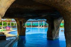 Приглашая взгляд золотого грота гостиницы тюльпана в бассейне и земель при люди ослабляя в предпосылке на солнечный день Стоковые Фотографии RF