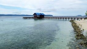 2 приглашая голубого дома дока настелинного крышу около seashore с голубой предпосылкой холмов Стоковое фото RF