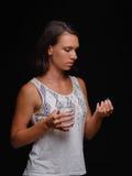 Пригонка резвится девушка принимая витамины или давать допинг Пациент принимая лекарства на черной предпосылке Унылый студент с а Стоковое Изображение