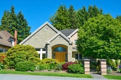 Пригородный жилой дом в зеленых деревьях и кустах на предпосылке голу стоковое фото