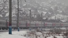 Пригородный поезд проходя на железнодорожный путь в сельской местности на зиме акции видеоматериалы