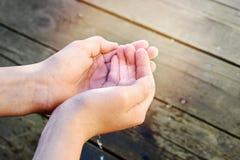 Пригорошня воды в руках ребенка стоковая фотография rf