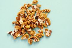 Пригорошня грецких орехов на голубой предпосылке стоковые фотографии rf