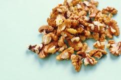 Пригорошня грецких орехов на голубой предпосылке стоковая фотография rf