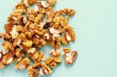 Пригорошня грецких орехов на голубой предпосылке стоковое фото
