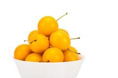 Пригорошня желтых слив вишни в керамическом шаре Стоковые Изображения