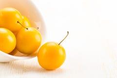Пригорошня желтых слив вишни в керамическом шаре Стоковые Фото