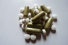 Пригорошня зеленых капсул moringa и белых таблеток Витамина K Стоковая Фотография RF