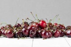 Пригорошня красных вишен на белом деревянном столе в pla хрустящей корочки стоковые фотографии rf
