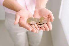Пригорошня монеток в руках мужчины ладони стоковое изображение