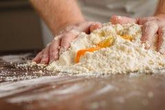 Пригорошня муки с яичком на деревенской кухне Против backg Стоковое фото RF