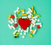 Пригорошня пилюлек и красное сердце на ярком colo сини бирюзы стоковая фотография rf