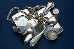Пригорошня серебряного миллиарда, silverware, украшений и старых серебряных монет на синей предпосылке стоковое фото rf