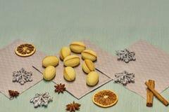 Пригоршня грецкого ореха сформировала печенья масла на серых салфетках, ручках циннамона, кусках высушенного апельсина и яблоке,  стоковое изображение