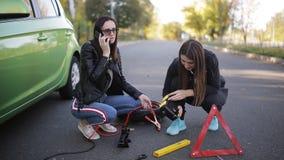 Придурковатая девушка пробуя исправить сломанный автомобиль на обочине акции видеоматериалы