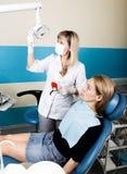 Прием находился на женском дантисте доктор рассматривает ротовую полость на спаде зуба Предохранение от костоеды доктор кладет Стоковые Фотографии RF