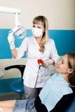 Прием находился на женском дантисте доктор рассматривает ротовую полость на спаде зуба Предохранение от костоеды доктор кладет Стоковые Изображения RF