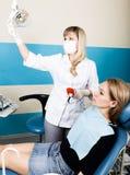 Прием находился на женском дантисте доктор рассматривает ротовую полость на спаде зуба Предохранение от костоеды доктор кладет Стоковое Изображение RF