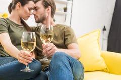 прижимаясь вино пар выпивая совместно на кресле стоковое изображение