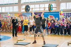 Признаковое представление тяжелоатлетов на чемпионате в черлидинг, молодой человек поднимает тяжелую штангу, вес штанги - 100 Стоковые Изображения RF