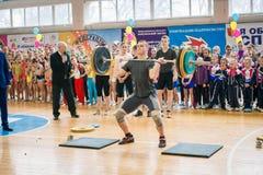 Признаковое представление тяжелоатлетов на чемпионате в черлидинг, молодой человек поднимает тяжелую штангу, вес штанги - 100 Стоковое Изображение RF