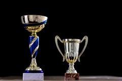 Приз, чашка стоя на таблице Награда чашки на черном backgro Стоковое Изображение RF