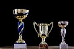 Приз, чашка стоя на таблице Награда чашки на черном backgro Стоковое Фото