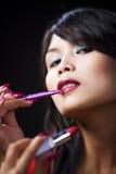 прикладывать губную помаду щетки используя детенышей женщины стоковое фото