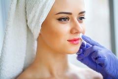 прикладывать политуру кожи внимательности прозрачную Опытный cosmetician вытягивая вне чела стоковые изображения rf