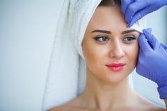 прикладывать политуру кожи внимательности прозрачную Опытный cosmetician вытягивая вне чела стоковые изображения