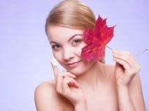прикладывать политуру кожи внимательности прозрачную Сторона девушки молодой женщины с красным кленовым листом Стоковая Фотография