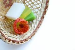 прикладывать политуру кожи внимательности прозрачную Handmade крупный план мыла и цветка в плетеной корзине белая предпосылка, ко стоковое изображение rf