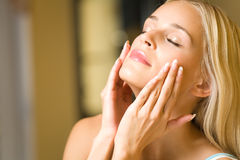 прикладывать cream лицевую женщину Стоковая Фотография