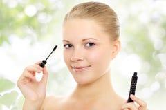 прикладывать mascara зеленого цвета девушки предпосылки Стоковая Фотография RF