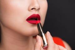 прикладывающ губу лоска сделайте профессионала вверх Привлекательная азиатская модель прикладывая красное lipsti Стоковое Изображение