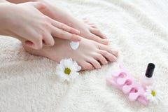 прикладывающ cream ноги ее женщина Стоковые Изображения RF