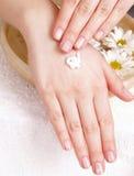 прикладывающ cream руки она к женщине Стоковая Фотография RF