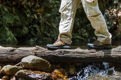 Приключение концепции образа жизни перемещения влажных ботинок пешее, пересекает поток стоковые фотографии rf